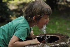 Trinkwasser des kleinen Jungen vom Hahn im Park stockfotos