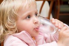 Trinkwasser des kleinen Mädchens Stockbilder