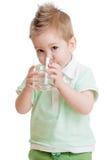 Trinkwasser des Kleinkindes oder des Kindes vom Glas Lizenzfreie Stockbilder