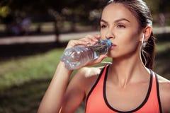 Trinkwasser des müden Mädchens nach hartem Training Stockfotografie