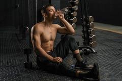 Trinkwasser des Mannes nach hartem Training lizenzfreie stockbilder