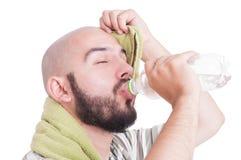 Trinkwasser des Mannes und Abwischen der verschwitzten Stirn Stockbild