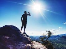 Trinkwasser des Mannes von der Plastikflasche in den schönen Bergen lizenzfreie stockfotos