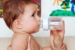 Trinkwasser des Schätzchens von der Flasche Stockbilder