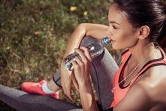 Trinkwasser des schönen Mädchens, nach draußen ausbilden Stockbilder