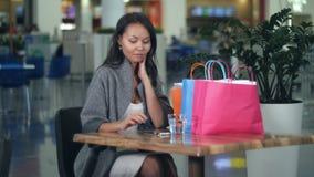 Trinkwasser des schönen Mädchens und mit Smartphone nach dem Einkauf im Mall stock video footage