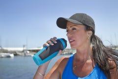 Trinkwasser des sportlichen Mädchens draußen lizenzfreie stockfotografie
