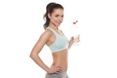 Trinkwasser des sportlichen Mädchens von einer Flasche nach einem Training, Eignungstraining, lokalisiert auf weißem Hintergrund Stockfotografie