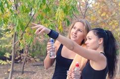 Trinkwasser mit zwei geeigneten Athleten der jungen Frauen lizenzfreie stockbilder