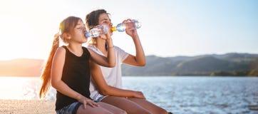 Trinkwasser mit zwei Mädchen und Sitzen durch das Meer Stockfotografie