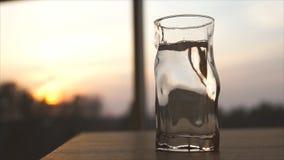 Trinkwasser wird in ein Glas bei Sonnenuntergang gegossen Flasche und Glas mit Minze- und Eisfelsen stock video