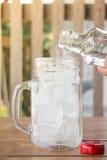 Trinkwasser wird in gefrorenes Glas gegossen lizenzfreie stockfotos