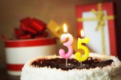 Trinta e cinco anos de aniversário Bolo com velas e os presentes ardentes Imagens de Stock