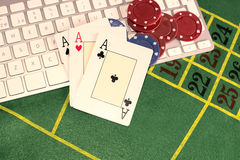 Trio of aces with poker pieces on a computer keyboard Stock Images