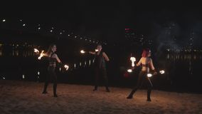 Trio of artists dancing with lit staves at night stock video