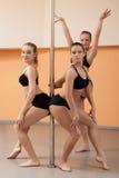 Trio av nätta unga dansare som poserar med pylonen Arkivfoton