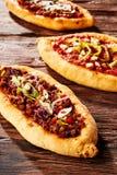 Trio av nytt bakade pizzaloaves på tabellen arkivfoto