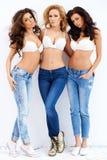 Trio av sexiga välformade kvinnor i jeans och behå Arkivbild
