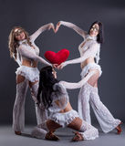 Trio of beautiful go-go dancers posing as cupids Stock Photography