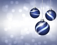 Trio of Blue and Silver Christmas Ornaments on Twinkling Backgro Royalty Free Stock Photos