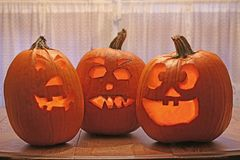 A trio of carved pumpkins illuminated from inside royalty free stock photography