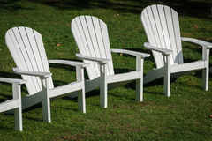 Trio of Chairs. Three Adirondack chairs on the lawn Stock Photo