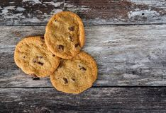 Trio of choc chip cookies seen fresh from the oven, on a rustic kitchen table. These large, home baked cookies are seen on a rustic wooden table, having just Royalty Free Stock Images