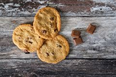 Trio of choc chip cookies seen fresh from the oven, on a rustic kitchen table. These large, home baked cookies are seen on a rustic wooden table, having just Royalty Free Stock Image