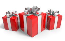 Trio of Christmas gifts neatly wrapped in silver ribbons Royalty Free Stock Images