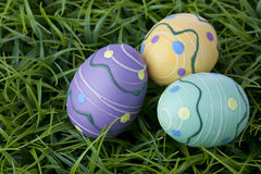 Trio of colorful Easter eggs laying in bright green grass. Stock Photos