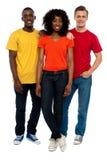 Trio de jeunes amis occasionnels posant dans le type Image stock