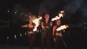 Trio des artistes de fireshow avec les torches allumées par la rivière banque de vidéos