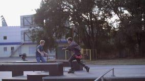 Trio di HD: Il motociclista, pattinatore, pattinatore del rullo sta facendo i trucchi sulla terra video d archivio