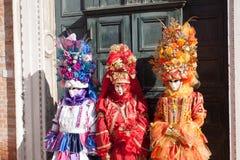 Trio die van Carnaval-kostuums met gekleurde kleding op bloemen en vruchten lijken die in Venetië Carnaval stellen Stock Fotografie