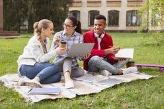 Trio dos estudantes espertos que preparam-se para o exame internacional no parque foto de stock
