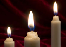 Trio of fire. Three candles burning in a row royalty free stock photo