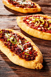 Trio of freshly baked pizza loaves on table stock photo