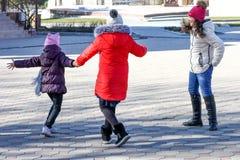 Trio gelukkige tieners op een zonnige dag die rond in de yard voor de gek houden royalty-vrije stock fotografie