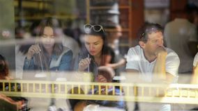 Trio of happy friends having a good time at dinner table in cafe with cocktails in the city. two women and one man in. Restaurant seen through window on the stock footage
