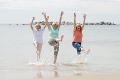 Trio hogere rijpe teruggetrokken vrouwen op hun jaren '60 die pret hebben die samen van het gelukkige lopen op strand speels glim stock foto's