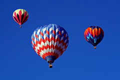 A Trio of Hot Air Balloons. Three colorful hot air balloons hang in a beautiful blue sky Royalty Free Stock Photos