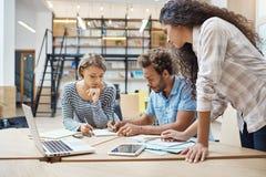 Trio jonge multi-etnische succesvolle bedrijfsmensen die in het coworking van ruimte zitten, die over nieuw project spreken van stock foto