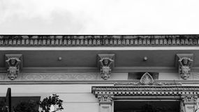 A trio of male figures holding the building. Shot in black and white detail on the sculpture on the facade of this historic building representing some characters royalty free stock images