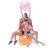 Trio of merry beautiful sportswomen in studio Royalty Free Stock Photo