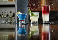Trio of Mixed Drinks. A trio of three mixed beverages and a menu in a restaurant Stock Images