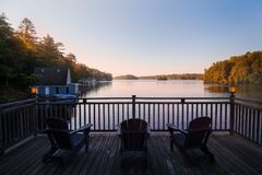 Trio of Muskoka chairs on a patio overlooking Lake Joseph at dawn. royalty free stock image