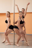 Trio of pretty young dancers posing with pylon Stock Photos