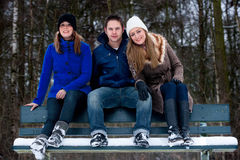 Trio sitting on a parkbench in winter Stock Photos