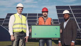 Trio of solar panel engineers outside. Close shot of trio of solar panel engineers with green screen panel and executive surrounded by large collector arrays stock footage