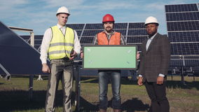 Trio of solar panel engineers outside. Trio of solar panel engineers with green screen panel and executive surrounded by large collector arrays outside stock footage